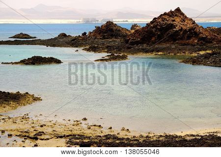 View on a lagoon with transparent water and volcanic cliffs on the Canary island Lobos in Spain. On the background there is the sand beach of Corralejo on Fuerteventura.