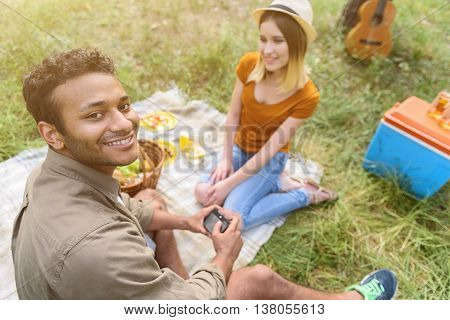 Cheerful man and woman making picnic in nature. They are sitting on blanket and smiling. Guy is looking at camera happily