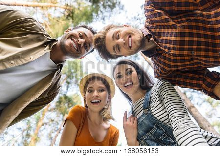 Low angle of happy four friends resting in forest together. They are standing and looking at camera with joy. Men and women are smiling