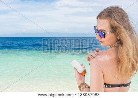 young woman applyng sun protector cream on her hand on the beach close to tropical turquoise sea under blue sky at sunny day