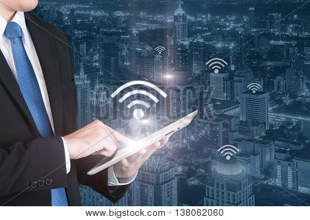 Business technology concept - Business man press digital tablet to connecting wifi or internet in business center district.