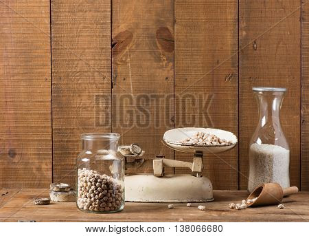 Vintage kitchen scale weighing chickpea on wooden background.