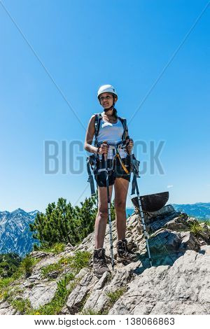 Confident female young hiker in helmet and climbing gear at rocky summit in wilderness under blue sky with copy space