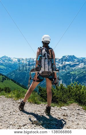 Back view on single female hiker in helmet and shorts with backpack and hiking equipment across the valley from tall mountains