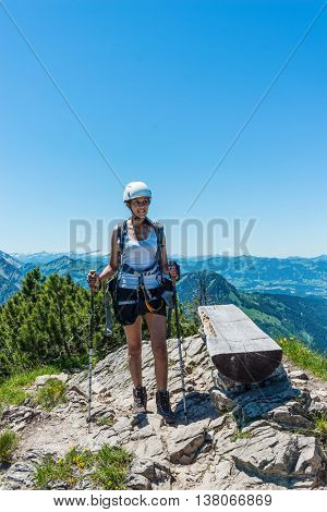 Single young adult woman in white helmet, shorts and tee shirt with confident expression, holding hiking sticks as she stands beside log bench at mountain summit
