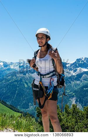 Young Indian woman in mountaineering gear standing on an alpine summit looking into the distance with a backdrop of snowy alps