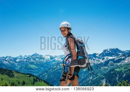 Smiling young woman in short pants, shirt, hiking backpack and helmet standing in foreground of mountain scene with copy space