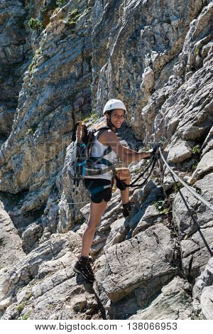 Smiling fit young female mountaineer standing on a steep rocky slope holding onto ropes turning to smile at the camera