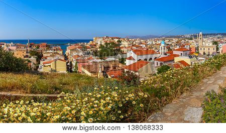 The medieval city with Orthodox cathedral Trimartiry and lighthouse in old harbour, panoramic aerial view from Schiavo Bastion in the sunny morning, Crete, Greece