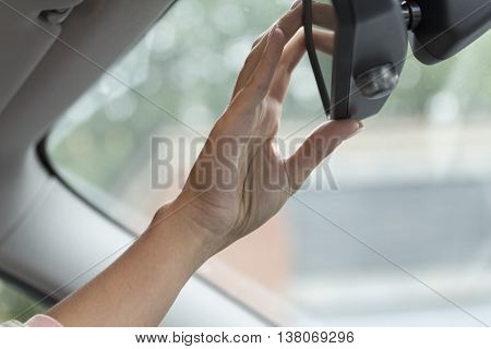 girl adjusts the rear view mirror in a car