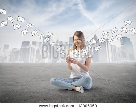 Smiling woman sending sms from a mobile phone with cityscape on the background