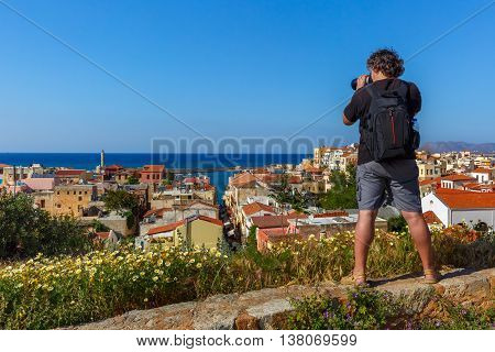 Photographer takes picture of medieval city with with lighthouse in old harbour from Schiavo Bastion in the sunny morning, Crete, Greece