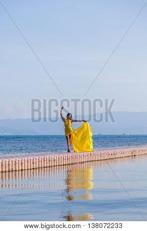 Woman in flying yellow dress on pontoon bridge
