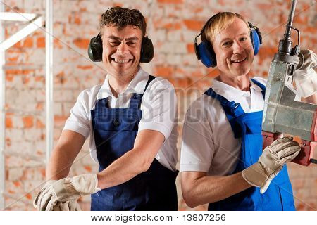 Two construction workers standing in a construction site in front of a brick wall. Their are wearing ear protection, one is carrying an air hammer