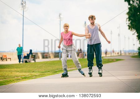 Active people modern couple exercise together and have fun. Relaxing hobby. Young people hold hands while rollerblading in park.