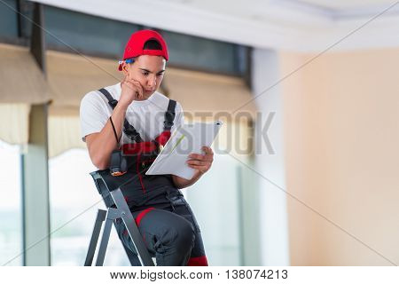 Young repairman checking the drawings before starting the work