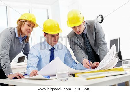 Three architects sitting at table and looking at a project