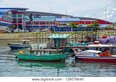 Labuan,Malaysia-July 11,2016:Fisherman jetty with small boats with background of Labuan UTC at Market Sentral,Labuan on 11th July 2016.The fishing industry contributes income to islanders here.