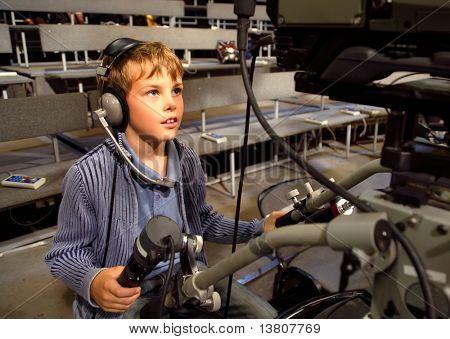 Kleiner Junge mit Kopfhörer und Mikrofon sitzt auf der professionellen Video-Kamera im Auditorium Tel