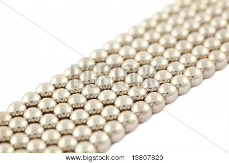 Bar which lies bias consisting of silvery beads on  white background