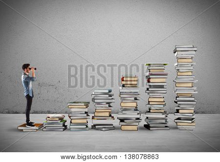 Boy with binoculars on a scale of books