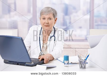 Senior female doctor, working at desk, using laptop computer. Looking at camera.?