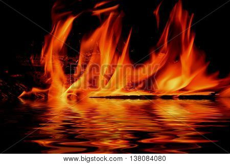 Picturesque flames from a fire on a black background with reflection in water