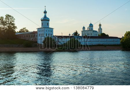 Architecture landscape - towers and cathedrals of Yuriev male monastery on the bank of the Volkhov river in Veliky Novgorod Russia sunset summer architecture view in the backlight