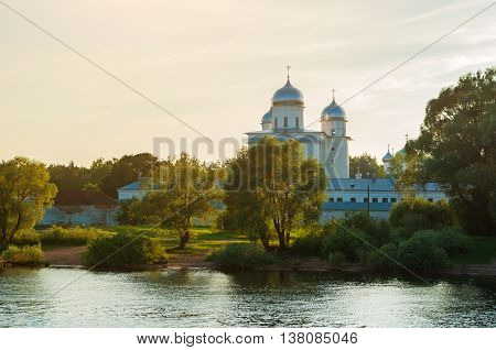 Architecture sunset summer landscape of architecture landmark- St George cathedral of Yuriev monastery near the Volkhov river in Veliky Novgorod Russia. Sunset summer architecture view in backlight
