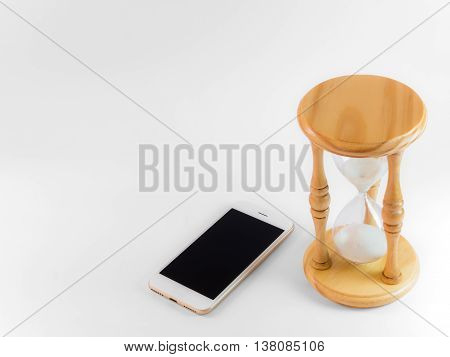 Smart phone and hourglass isolate on white with clipping path and copy space. Concept of smart phone take much time smart phone addiction phubbing game or social media issues.