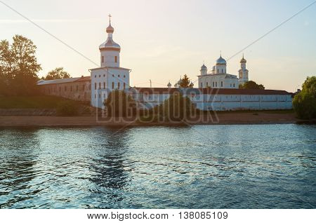 Sunset architecture landscape - view of towers and cathedrals in Yuriev male monastery on the bank of the Volkhov river in Veliky Novgorod Russia sunset summer architecture view in the backlight