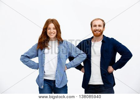 Cheerful redhead girl dressed in blue shirt and white t-shirt with boy dressed in white t-shirt and dark-blue jacket standing over white background.