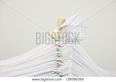 Wooden Dummy Holding House On Top Of Pile Overload Document