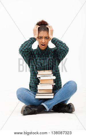 Portrait of upset young beautiful african girl in green blouse and jeans looking at camera, sitting on floor with books over white background.