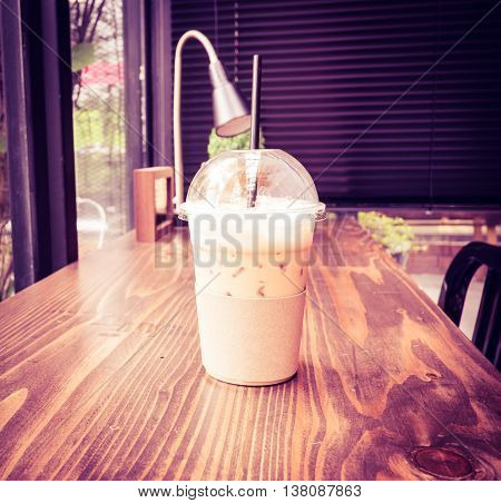 Vintage Filter :ice Coffee On Wood Table Beside Window In Coffee Shop At Garden