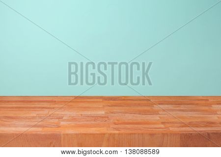 Empty wooden kitchen counter over mint wall background for product montage display