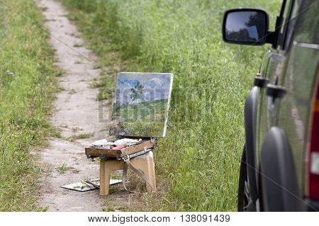 A wooden artist box with unfinished artwork standing on a chair next to a parked car. Concept of travel and paint outdoor cropped shot
