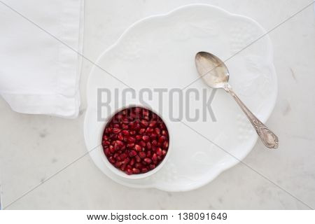 Top-down view of pomegranate seeds in a small bowl set on a dessert plate on white marble with napkin and silver sppon.