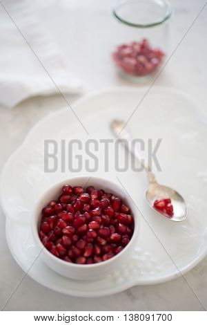 Front view and shallow depth of field on a small bowl of pomegranate arils (pomegranate seeds) set on a dessert plate with an elegant silver spoon. A small container of arils sits in the backgroud in bokeh.