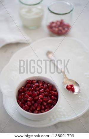 Shallow depth of field on a small bowl of pomegranate arils (pomegranate seeds) set on a dessert plate with an elegant silver spoon. More arils and yogurt sit in the backgroud in bokeh.