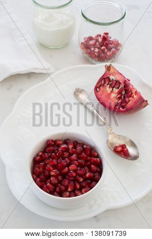 Small bowl of pomegranate arils (pomegranate seeds) set on a dessert plate with an elegant silver spoon and a quartered pomegranate. Shot at f/32 with focus throughout. More arils and a container of yogurt sit in the backgroud.