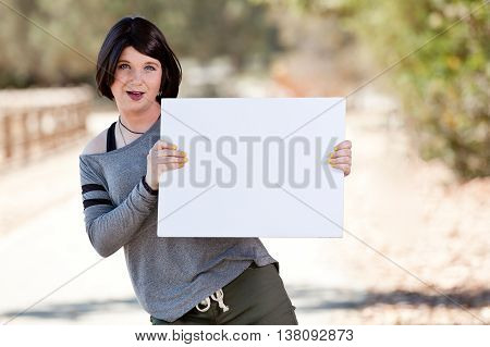 Short black haired Transgender girl holding blank poster board.