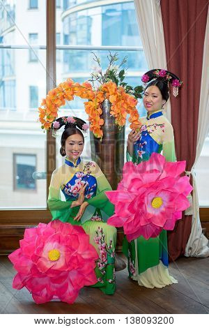 Two Chinese Girls In Traditional Style Clothes With Parasols As A Lotus Flowers