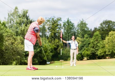 Senior woman practicing with golf pro