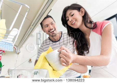 Asian couple washing the dishes after breakfast, meal, man helping his wife
