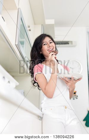 Indonesian woman eating cookies in her kitchen