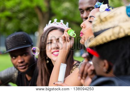 Young Indian girl blowing soap bubbles between multicultural group sitting in park on lawn