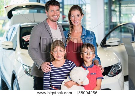 Family with children buying new car at auto dealership, mom, dad and kids standing in showroom