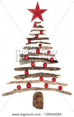 Abstract driftwood christmas tree with red star and bauble decorations over white background.