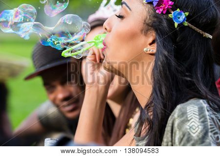 Indian girl blowing soap bubbles, young african man with basecap in background
